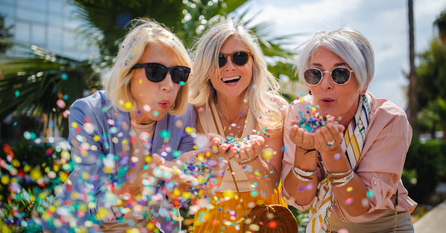 Happy women blowing confetti